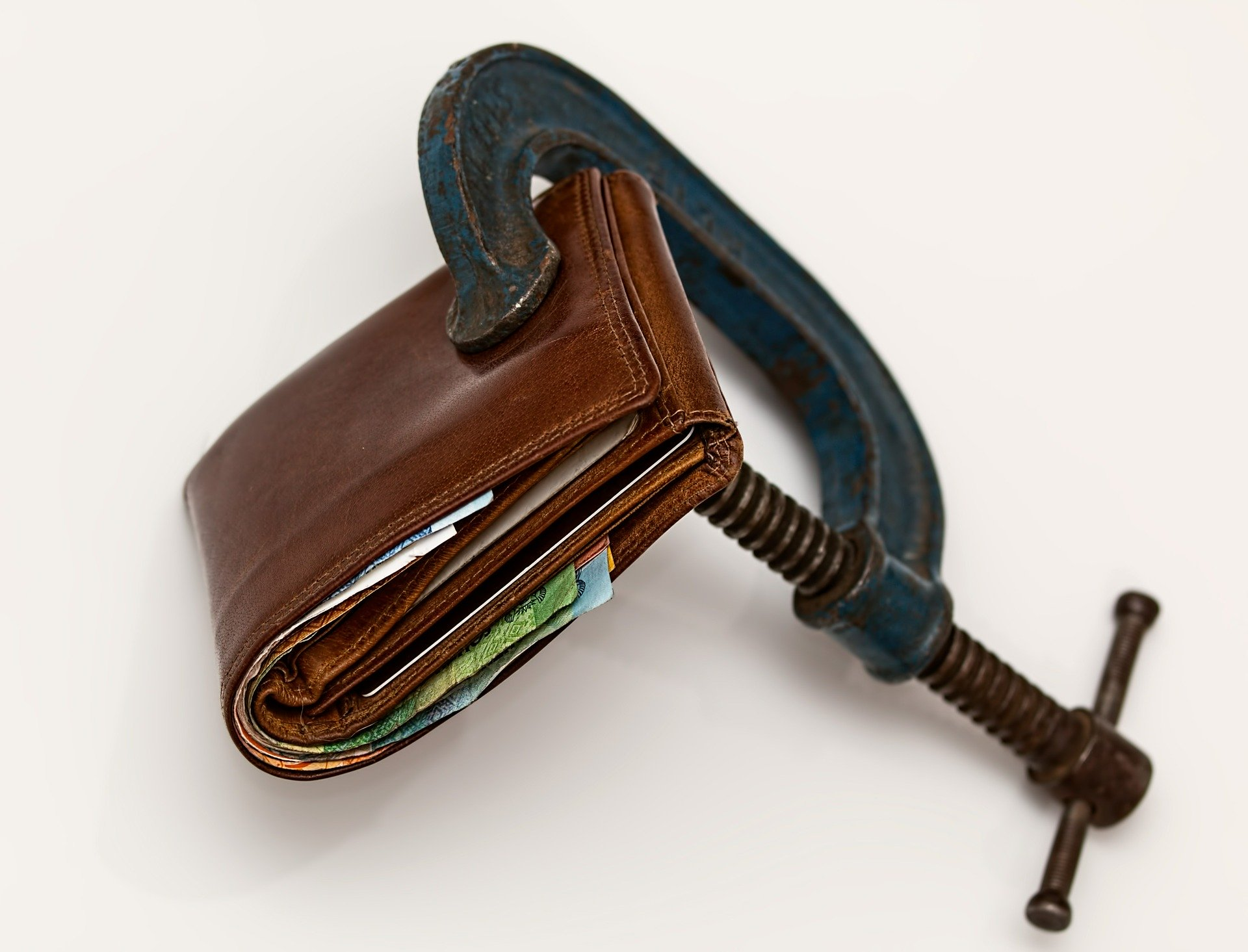 """A wallet in a vice, used to represent the concept of """"consumer proposal vs. debt consolidation."""""""